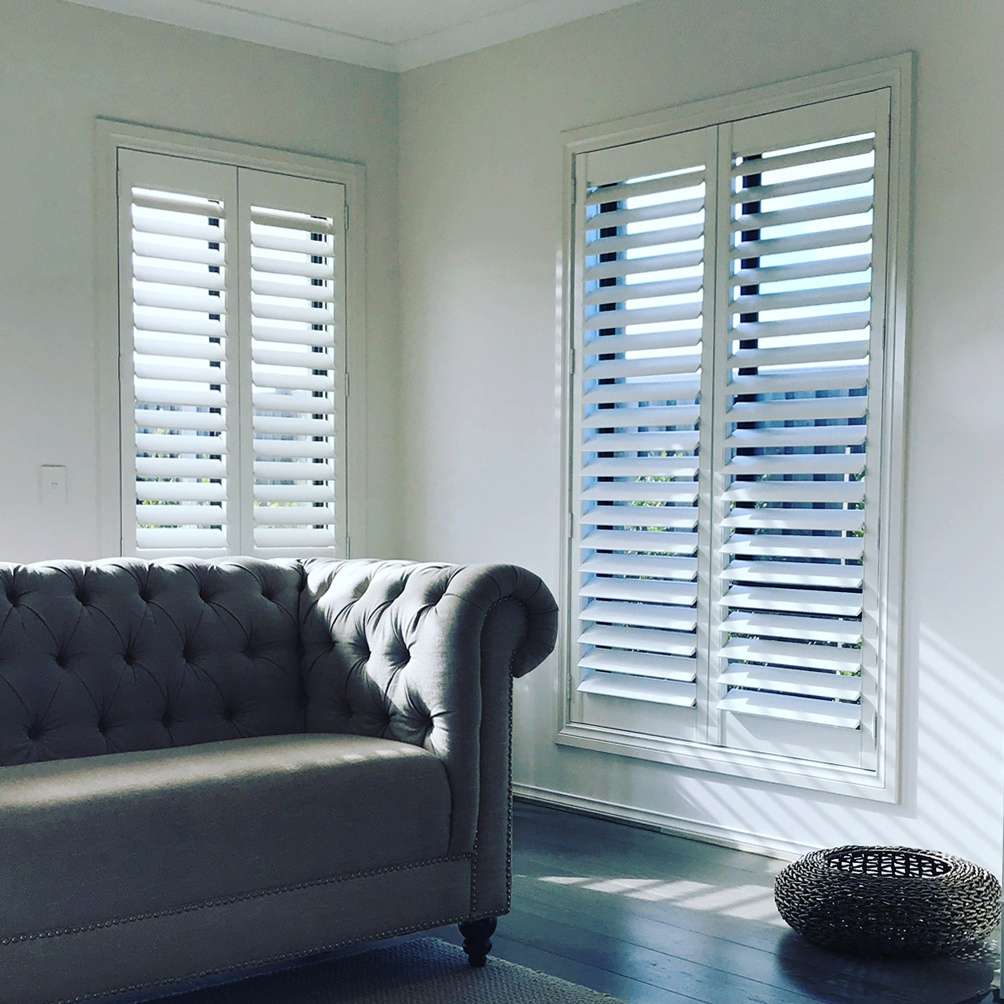 A picture of a couch and some white plantation shutters.